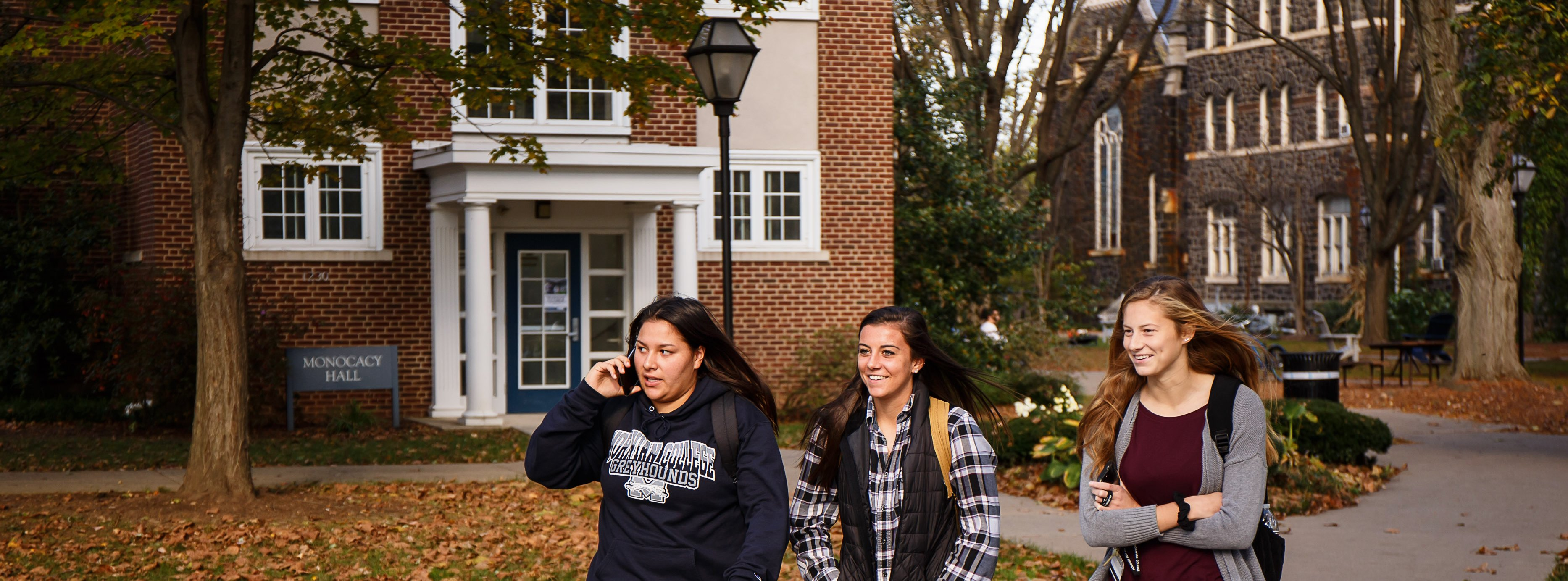 Three students walk in a group out front of Monocacy Hall.