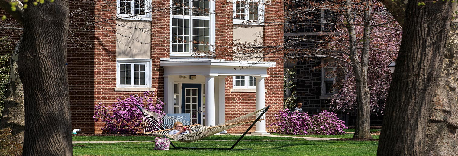 A student lounges on a hammock in front of Monocacy Hall.