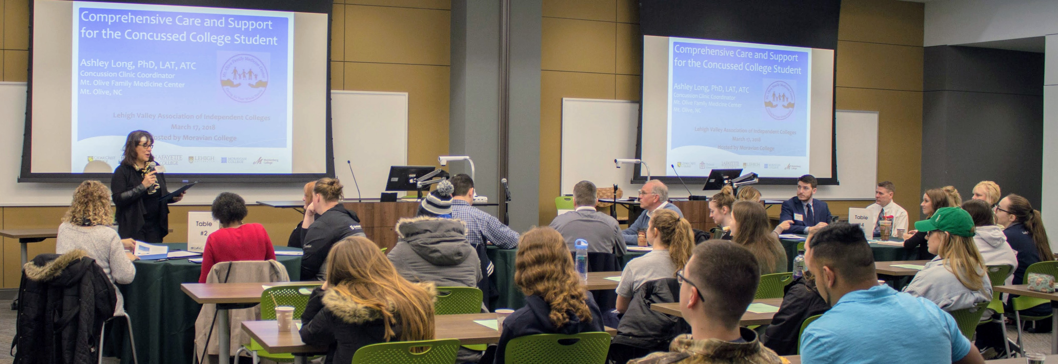 Barbara Ryan Hausman, Director of Academic & Accessibility Support, stands at the front of a large room. She is welcoming a group of students, faculty, and staff members who are sitting at tables in the room in front of her. A PowerPoint slide displaying the conference title, the Comprehensive Care and Support for the Concussed College Student conference, and the name of the presenter, Ashley Long, is projected onto two screens behind Barbara.