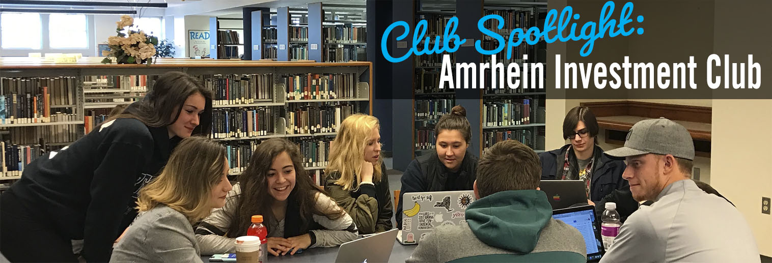 students gather around table in library to study stocks and investments