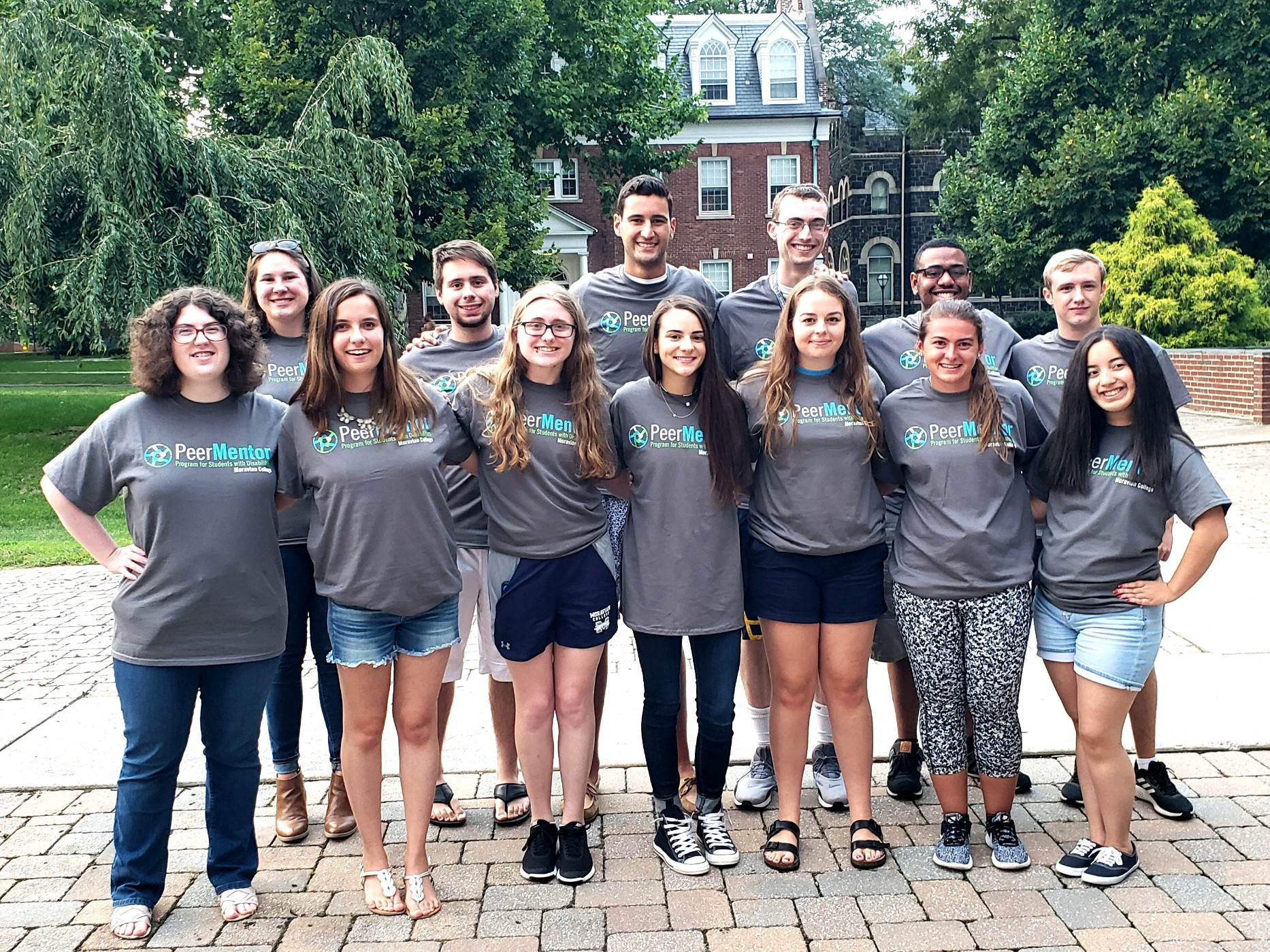 "A group of 13 students wearing matching grey t-shirts stand outside posed for a group photo. Their t-shirts read ""Peer Mentor Program for Students with Disabilities, Moravian College"""