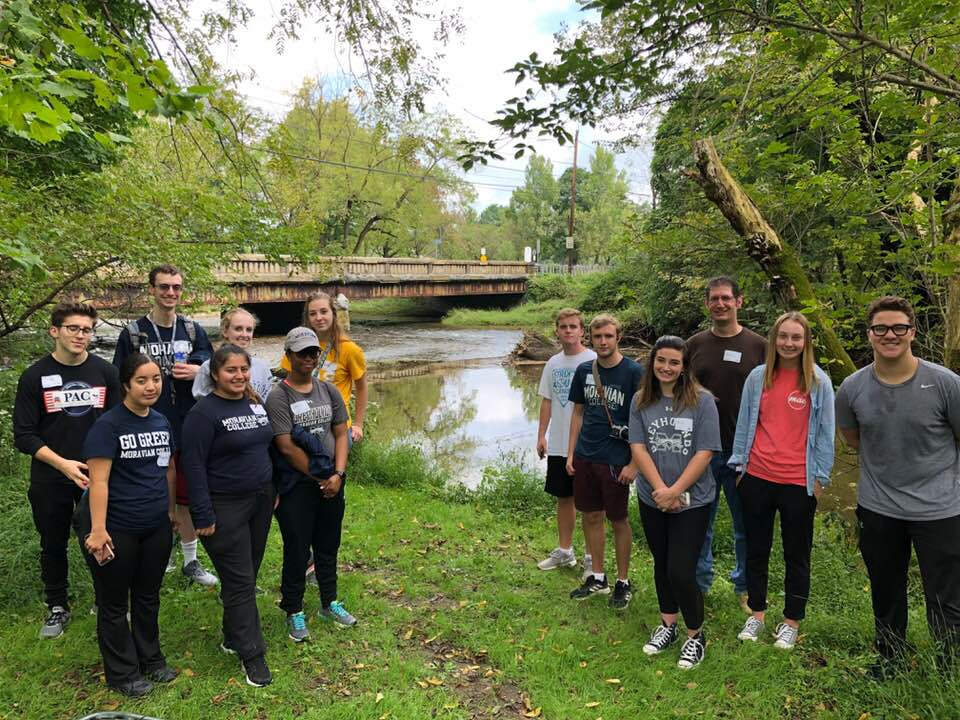 Students clean up the Heller Homestead Park and buildings during Heritage Day. Students are posed for a photo along the creek bed.