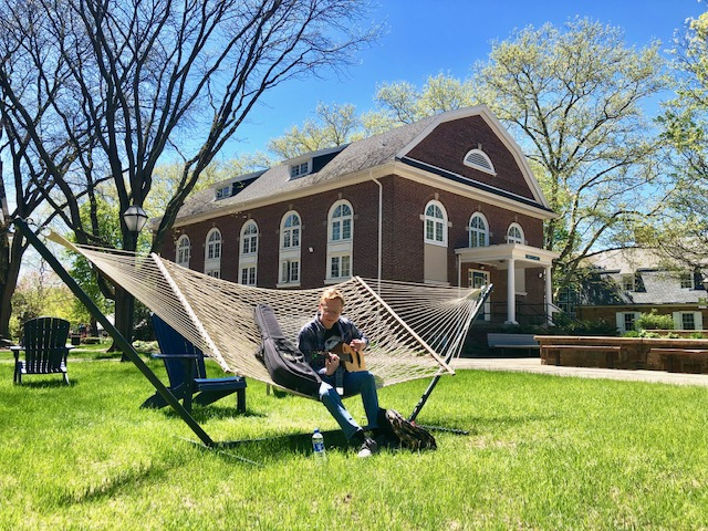A male student sits on a hammock outside in the quad between 3 campus buildings. A flowering white dogwood tree appear above the roofline of the building behind him. The grass is green.