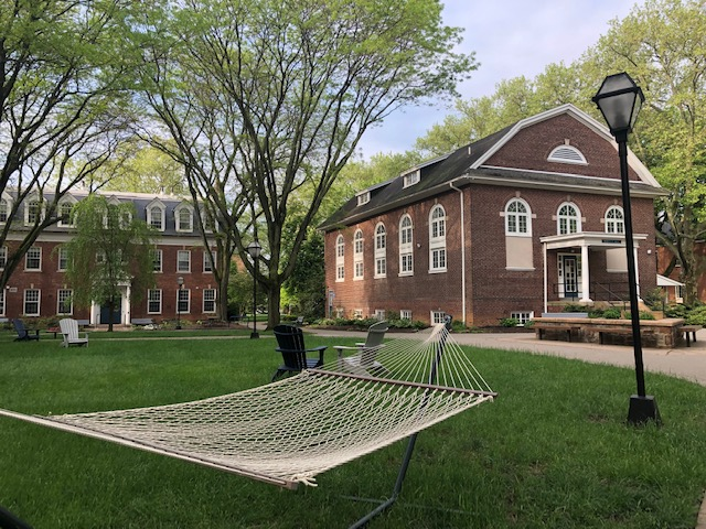 A hammock sits in the sum outside in the quad between 3 campus buildings. A flowering white dogwood tree appear above the roofline of the building behind him. The grass is green.