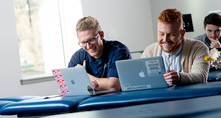 Two students using their macbooks