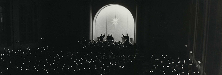 History of the Moravian College Christmas Vespers Banner featuring black and white image of large congregation from behind holding up candles in the dark.