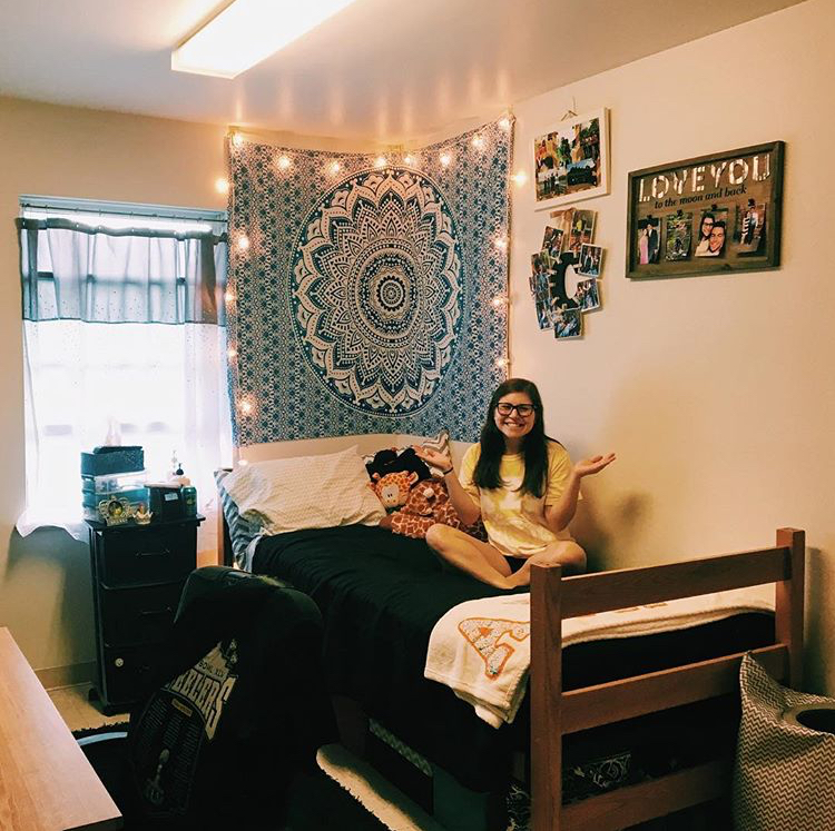 Student sitting in their dorm room with blue and white tapestry hung on the wall
