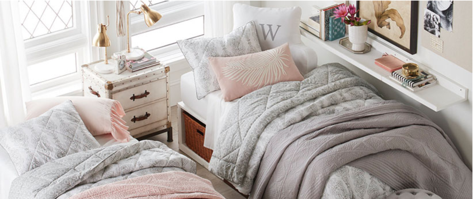 Image of Pottery Barn light pink and grey bedding in mock dorm room with gold lamp, white bedside table, and decorative pink throw pillow with white feather