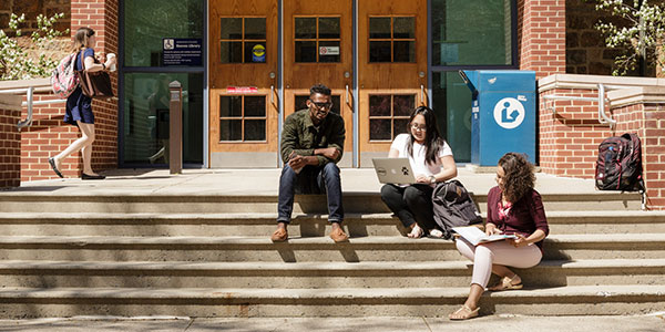 Three students sitting on the steps of Reeves Library