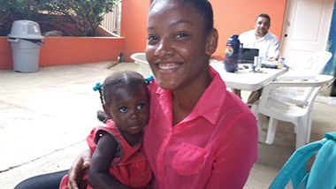 A girl from the orphanage Niños de Cristo holds a new arrival