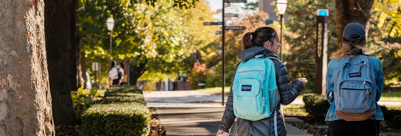 Two students walk though campus with backpacks on