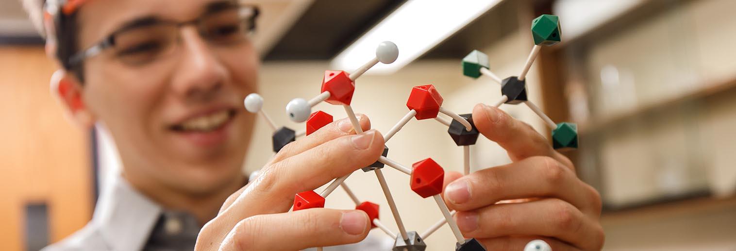 Chemistry student holding a model