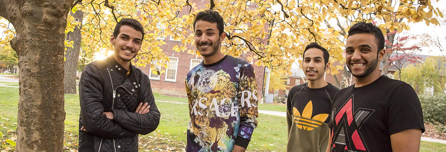 four international students smiling on campus