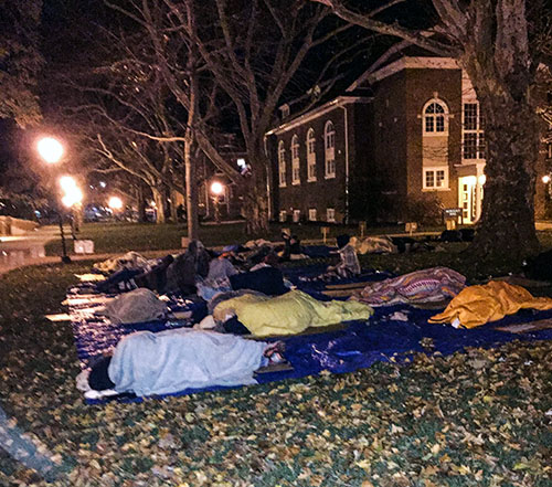 Rows of students sleeping on tarps and cardboard at Moravian College Sleep Out