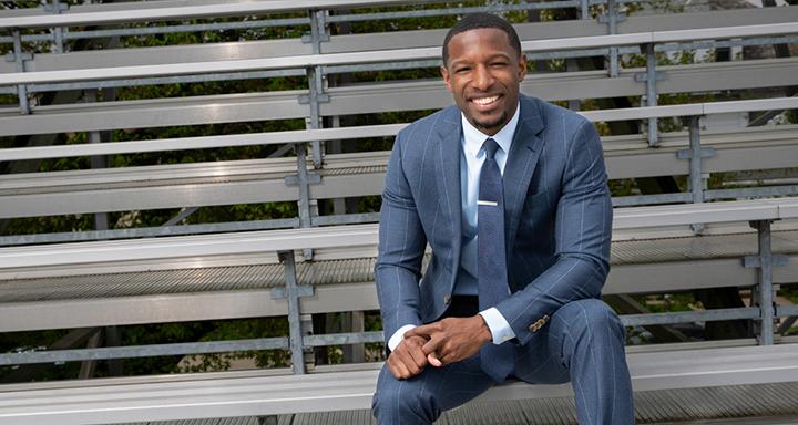 Kahron Walker in a suit, sitting on bleachers
